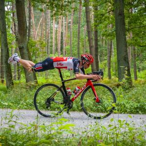 Rowerzysta jedzie prawie leżąc na rowerze przez las