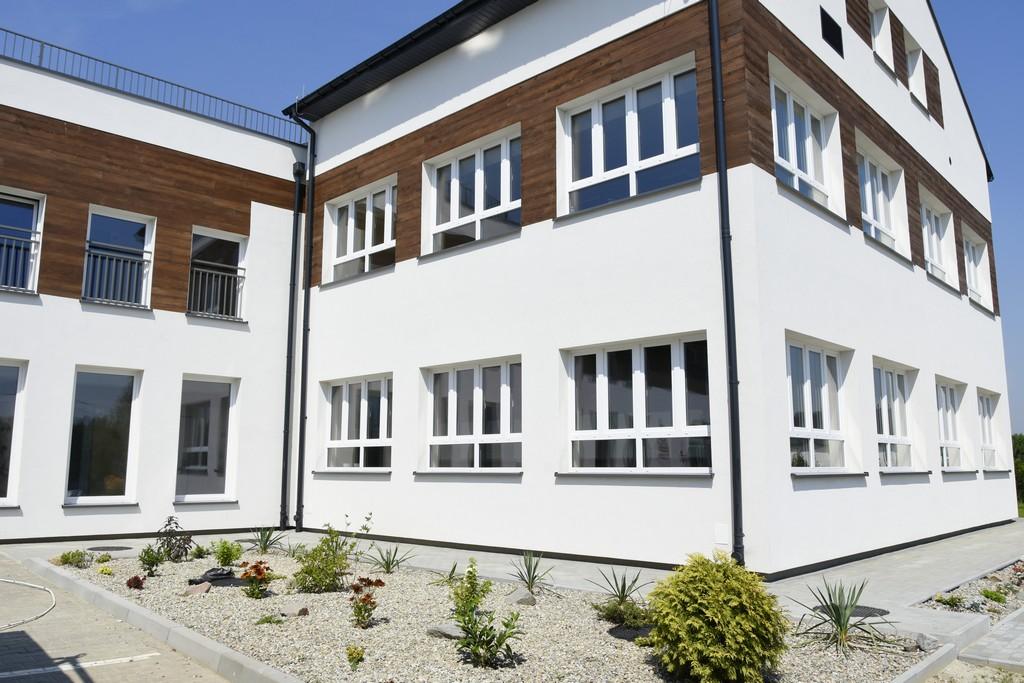 Fragment wyremontowanego budynku szkoły podstawowej w Zakrzowie. w kolorach białym i brązowym