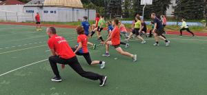Kilka osób rozgrzewa nogi przed treningiem