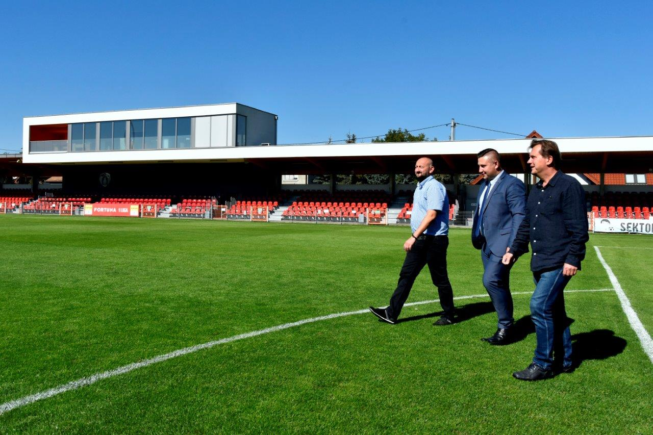 Pełniący funkcję burmistrza Niepołomic Krystian Zieliński, prezes klubu Puszcza Niepołomice Jarosław Pieprzyca oraz dyrektor klubu Roman Koroza na murawie stadionu miejskiego.