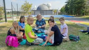 Grupa dzieci siedzi na trawie z instruktorką nieopodal obserwatorium astronomicznego.