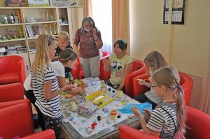 Dzieci uczestniczą w zajęciach plastycznych pod okiem instruktorki.
