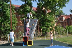 Dziewczynki na ściance do wspinaczki na placu zabaw przy szkole podstawowej.