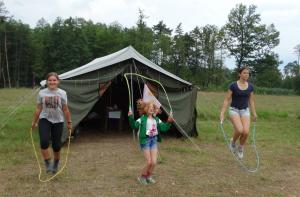Trzy dziewczyny w różnym wieku skaczą na skakankach.