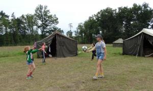 Dwie Dziewczyny grają w piłkę, dwie inne grają w badmintona.