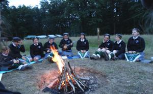 Harcerki siedzą w kręgu wokoło ogniska.