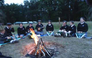Grupa harcerek siedzi wieczorem wokół ogniska.