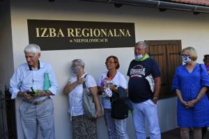 Grupa osób stoi pod napisem Izba Regionalna w Niepołomicach