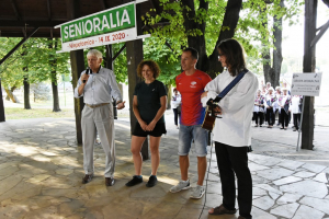 Janusz Jagła zapowiada ze sceny w parku gimnastykę dla seniorów