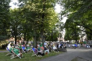 Kilkudziesięciu seniorów siedzi na leżakach w parku miejskim