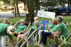 Grupa seniorów ze Stowarzyszenia Wielicki Uniwersytet Trzeciego Wieku na leżakach w parku miejskim