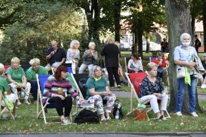 Grupa seniorów na leżakach w parku słucha występu na scenie