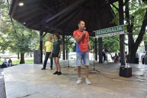 Trener Ilya Markov ze sceny w parku prowadzi wspólną gimnastykę