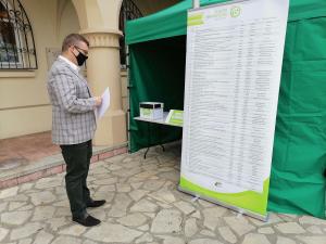 Michał Hebda, zastępca burmistrza czyta listę projektów do budżetu obywatelskiego w stacjonarnym punkcie do głosowania