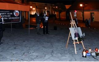 Kilka osób stoi przy fontannie w Rynku. Na pierwszy planie plansza z fotografią Piotra Szczęsnego