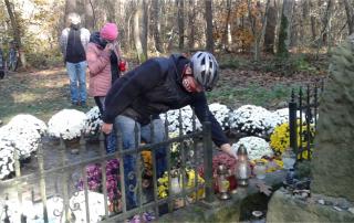 Delegacja TKKF Wiarus kładzie znicz przy pomniku w do Miejscu Martyrologii Żydów w Puszczy Niepołomickiej.