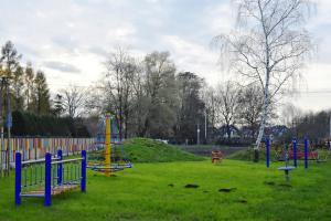Gotowy plac zabaw. Na placu widać zamontowane urządzenia, posadzone krzewy i zasianą trawę