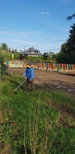 Mieszkaniec osiedla kosi trawę, trwają prace porządkowe po montażu urządzeń.