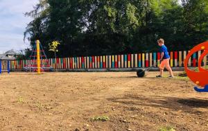 Chłopak wyrównuje walcem teren przed posianiem trawy. Na placu zamontowane są już linarium stożek i helikopter na sprężynie.