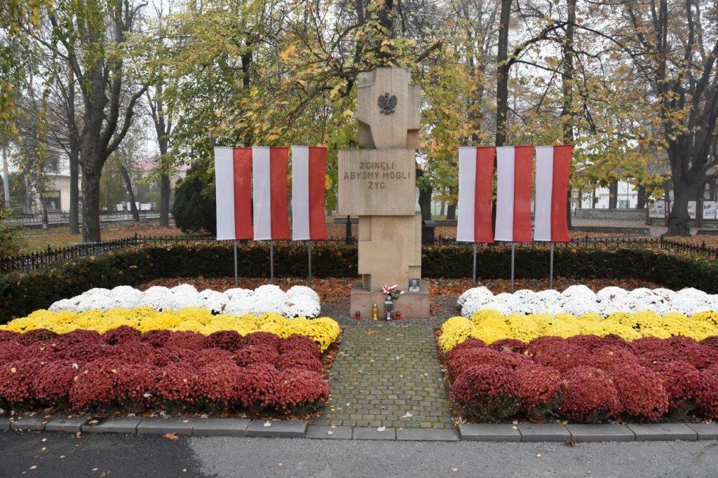 Chryzantemy ułożone w kolorach flagi Niepołomic: czerwonym, żółtym i białym przed pomnikiem przy parku miejskim
