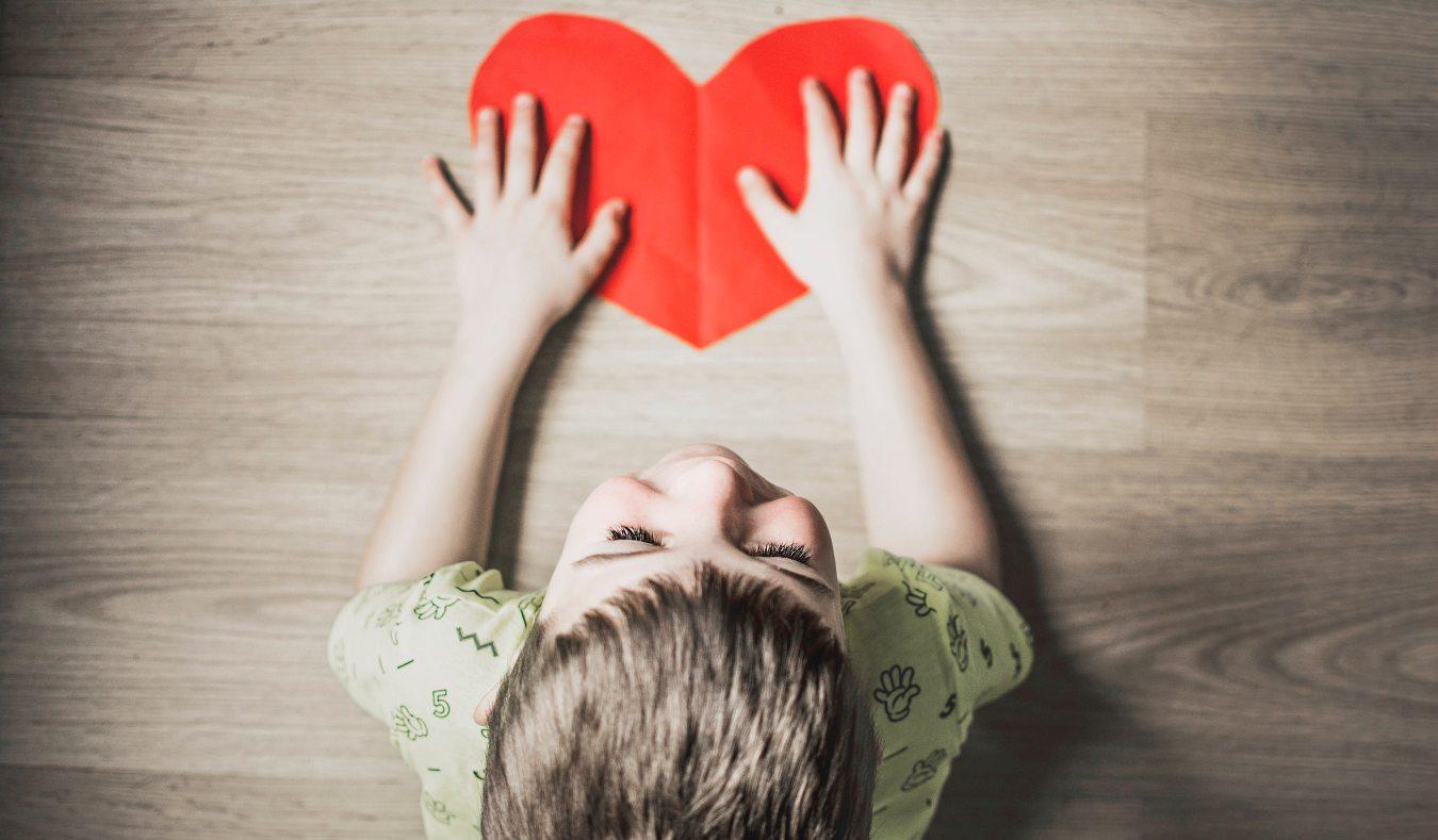 Dziecko siedzi na podłodze, w rękach trzyma czerwone serce z papieru