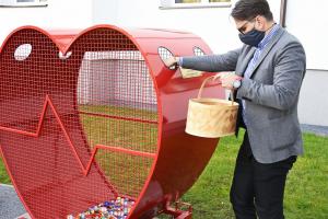 Burmistrz Roman Ptak napełnia serce przy szkole w Podłężu plastikowymi nakrętkami