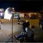 Nagrywanie wywiadu na placu przy remizie OSP Niepołomice, na którym znajduje się wóz strażacki i dwie osoby podczas nagrania.