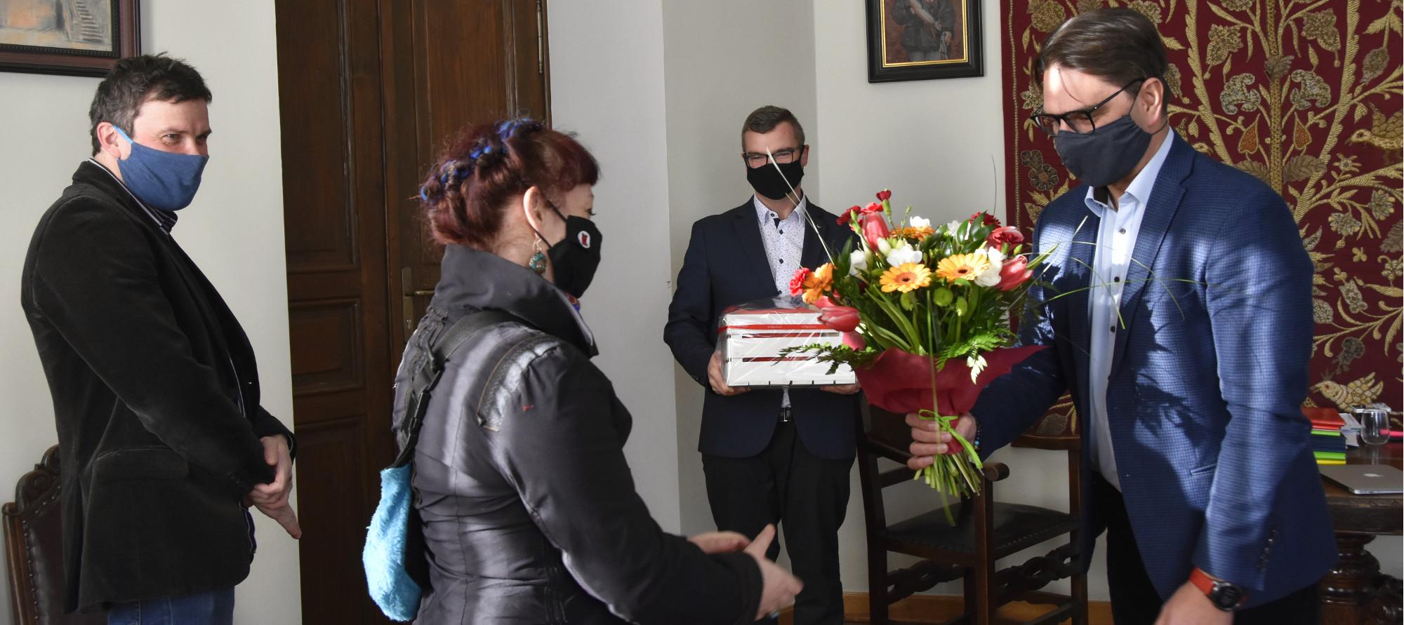 Burmistrz Roman Ptak wręcza kwiaty autorce muralu