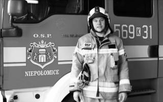 Krzysztof Haniszewski w uniformie strażackim na tle samochodu pożarniczego