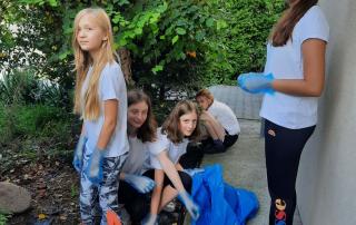 uczniowie sprzątający teren wokół szkoły