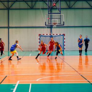 Drużyny kobiece rozgrywają mecz koszykówki.