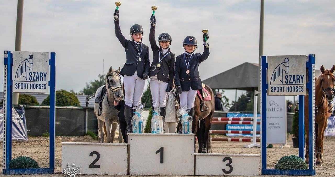 Zawodniczki zawodów konnych stoją na podium z pucharami